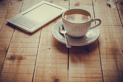 Eine Tasse Tee und ein ebook Leser auf einer hölzernen Tabelle Stockfotografie