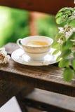 Eine Tasse Tee und eine Untertasse auf Veranda Lizenzfreie Stockbilder