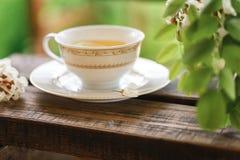 Eine Tasse Tee und eine Untertasse auf Veranda Stockfoto