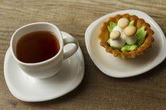 Eine Tasse Tee und einen Kuchen stockbild