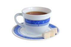 Eine Tasse Tee und Raffinade auf der Untertasse lokalisiert auf Weiß Lizenzfreies Stockfoto
