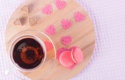 Eine Tasse Tee und eine Untertasse mit Erdbeerplätzchen zusammen mit Zuckerherzen und rosa Herzen auf einem hellen runden hölzern Lizenzfreies Stockfoto