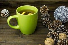 Eine Tasse Tee und Zitrone auf dem Hintergrund von neues Jahr ` s Landschaft Lizenzfreie Stockfotos