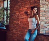 Eine tattoed sexy Blondine in einem T-Shirt und in einem Hut, die gegen eine Backsteinmauer aufwerfen Lizenzfreie Stockfotografie