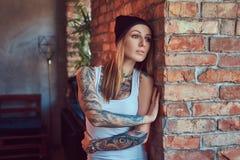 Eine tattoed sexy Blondine in einem T-Shirt und in einem Hut, die gegen eine Backsteinmauer aufwerfen Lizenzfreie Stockbilder