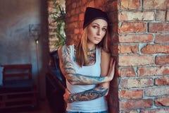 Eine tattoed sexy Blondine in einem T-Shirt und in einem Hut, die gegen eine Backsteinmauer aufwerfen Stockfotografie