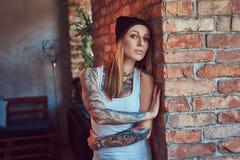 Eine tattoed sexy Blondine in einem T-Shirt und in einem Hut, die gegen eine Backsteinmauer aufwerfen Stockbild