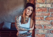 Eine tattoed sexy Blondine in einem T-Shirt und in einem Hut, die gegen eine Backsteinmauer aufwerfen Stockbilder