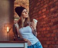 Eine tattoed sexy Blondine in einem T-Shirt und in einem Hut mit Tasse Kaffee in einem Raum mit Dachbodeninnenraum Stockbild