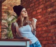 Eine tattoed sexy Blondine in einem T-Shirt und in einem Hut mit Tasse Kaffee in einem Raum mit Dachbodeninnenraum Stockfoto