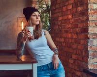 Eine tattoed sexy Blondine in einem T-Shirt und in einem Hut mit Tasse Kaffee in einem Raum mit Dachbodeninnenraum Lizenzfreie Stockfotografie