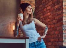 Eine tattoed sexy Blondine in einem T-Shirt und in einem Hut mit Tasse Kaffee in einem Raum mit Dachbodeninnenraum Stockfotos