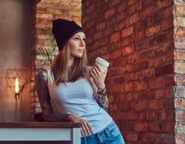 Eine tattoed sexy Blondine in einem T-Shirt und in einem Hut mit Tasse Kaffee in einem Raum mit Dachbodeninnenraum Stockbilder