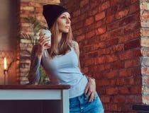 Eine tattoed sexy Blondine in einem T-Shirt und in einem Hut mit Tasse Kaffee in einem Raum mit Dachbodeninnenraum Lizenzfreie Stockfotos