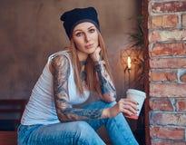 Eine tattoed sexy Blondine in einem T-Shirt und in einem Hut mit Tasse Kaffee in einem Raum mit Dachbodeninnenraum Lizenzfreie Stockbilder