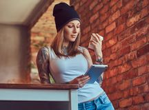 Eine tattoed sexy Blondine in einem T-Shirt und in einem Hut mit Tasse Kaffee und Tablet-Computer in einem Raum mit Dachbodeninne Lizenzfreies Stockfoto