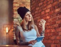 Eine tattoed sexy Blondine in einem T-Shirt und in einem Hut mit Tasse Kaffee und Tablet-Computer in einem Raum mit Dachbodeninne Lizenzfreie Stockfotos
