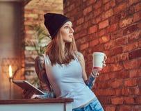 Eine tattoed sexy Blondine in einem T-Shirt und in einem Hut mit Tasse Kaffee und Tablet-Computer in einem Raum mit Dachbodeninne Stockbild