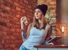 Eine tattoed sexy Blondine in einem T-Shirt und in einem Hut mit Tasse Kaffee und Tablet-Computer in einem Raum mit Dachbodeninne Stockfotografie