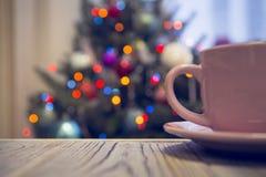 Eine Teeschale mit einer Untertasse auf einem Holztisch gegen verzierten Weihnachtsbaum Lizenzfreie Stockfotos
