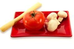 Eine Tomate, Pilze und Brot auf roter Servierplatte Stockbilder