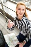 Eine touristische blonde Frau in der gestreiften Bluse, die in der Hand an der Station oder am Anschluss mit Karte sitzen und im  Lizenzfreie Stockfotos