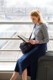 Eine touristische blonde Frau in der gestreiften Bluse sitzend an der Station oder am Ende und die Karte betrachtend Stockbild