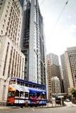 Eine Tram, die Passagiere befördert, überschreitet durch das Bank von China-Gebäude. Lizenzfreie Stockfotos