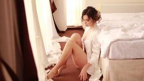 Eine traurige Braut im peignoir sitzt im Schlafzimmer auf Boden stock video