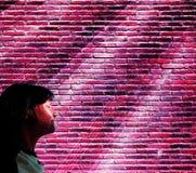 Eine traurige Frau mit geschlossenen Augen in den Strahlen des Neonlichtes stockbilder