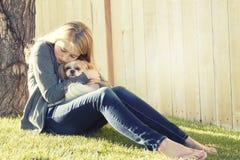 Eine traurige oder deprimierte Jugendliche, die einen kleinen Hund umarmt Lizenzfreie Stockfotografie