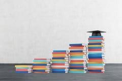 Eine Treppe wird von den bunten Büchern hergestellt Ein Staffelungshut ist auf dem letzten Schritt Lizenzfreies Stockbild