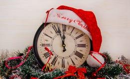 Eine Uhr mit einem Sankt-Hut und Weihnachtsdekorationen lizenzfreies stockbild