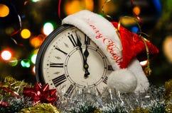 Eine Uhr mit einem Sankt-Hut und Weihnachtsdekorationen lizenzfreie stockfotos