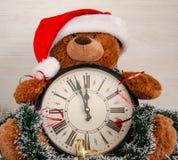 Eine Uhr mit Weihnachtsdekorationen und einem Spielzeugbären lizenzfreie stockfotografie