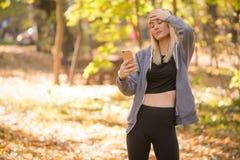 Eine Umkippenfrau hält ihren Handy gesorgt um die Mitteilung stockfoto