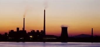 Eine umreiß einer Fabrik gegen Sonnenuntergang Lizenzfreie Stockfotos