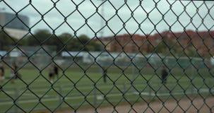 Eine unscharfe Gruppe Jungen, die Fußball am Gothia Cup üben Ein grüner Zaun im Vordergrund stock video footage