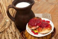 Eine Untertasse Käse backt mit Fruchtmarmelade, einem Topf Milch, einer Metallschale reifen roten Johannisbeeren und den reifen O Stockfotografie