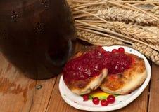 Eine Untertasse Käse backt mit Fruchtmarmelade, einem Topf Milch, einer Metallschale reifen roten Johannisbeeren und den reifen O Lizenzfreie Stockbilder