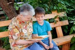 Eine Urgroßmutter liest ein Buch zum Urenkel Lizenzfreies Stockfoto