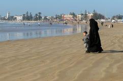 Eine völlig bedeckte moslemische Frau, die mit ihrem wenigen Sohn auf dem Strand geht stockbilder