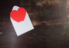Eine Valentinsgrußumschlagkarte mit einem roten Herzpapierc$haften Lizenzfreies Stockbild