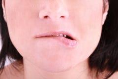 Eine verlegene Frau, die auf ihrer Lippe beißt Lizenzfreies Stockfoto