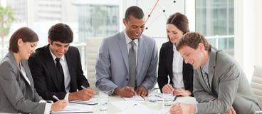 Eine verschiedene Geschäftsgruppe, die einen Haushaltsplan studiert Stockfotos