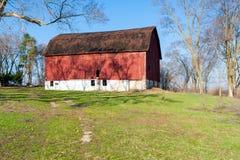 Eine verwitterte rote Scheune auf einem Hügel Lizenzfreie Stockfotografie