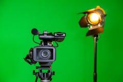 Eine Videokamera und ein Scheinwerfer mit einer Fresnellinse auf einem grünen Hintergrund Schmierfilmbildung im Innenraum Der Far lizenzfreie stockbilder