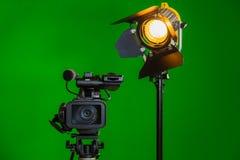 Eine Videokamera und ein Scheinwerfer mit einer Fresnellinse auf einem grünen Hintergrund Schmierfilmbildung im Innenraum Der Far stockfotos