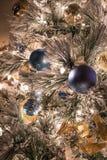Eine Vielzahl von Blau und Goldweihnachtsverzierungen auf einem gespritzten Weihnachtsbaum stockfotos