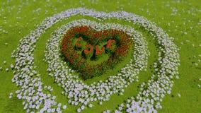 Eine Vielzahl von Blumen in Form eines Herzens auf einem grünen Feld, als Symbol Valentinsgruß ` s von Tag und von Liebe Lizenzfreies Stockbild